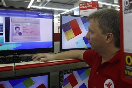A shop assistant looks at a screen broadcasting an image of the document which grants Edward Snowden temporary asylum status for a year, in Moscow August 1, 2013. REUTERS/Maxim Shemetov
