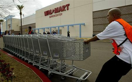 Employees move shopping carts as the first Wal Mart Supercenter to operate in the State of California, opened in La Quinta, California, March 3, 2004. REUTERS/Robert Galbraith