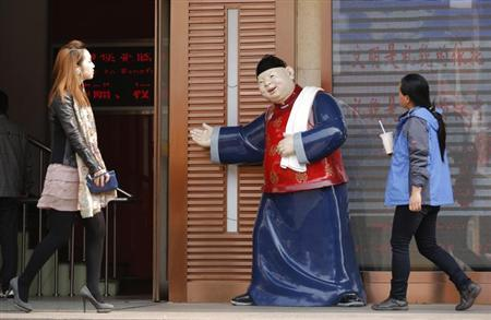 People walk past a statue, placed there to promote a restaurant, at a shopping district in Beijing April 3, 2013. REUTERS/Kim Kyung-Hoon/Files