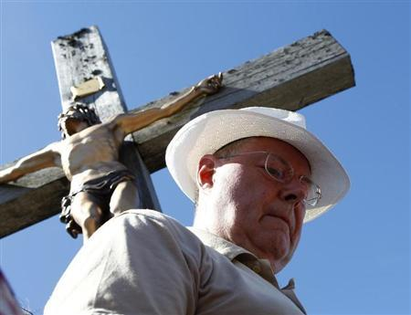 Peer Steinbrueck, the Social Democratic Party's (SPD) candidate for German Chancellor for the upcoming general election, stands next to a summit cross while hiking with regional SPD members and journalists during an election campaign tour, on Lusen mountain near Waldhaeuser in Bavaria August 1, 2013. REUTERS/Michaela Rehle