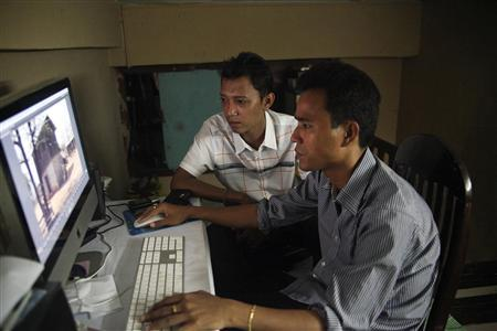 Movie director Zay Par (L) and his editor Zin Thaw work on their movie in the editing room in downtown Yangon July 19, 2013. REUTERS/Jared Ferrie