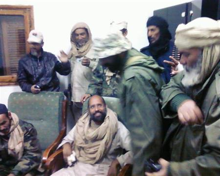 A mobile phone picture taken by one of his guards shows Saif al-Islam Gaddafi sitting with his captors in Obari airport November 19, 2011. REUTERS/Handout/Files