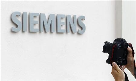 A photographer takes a picture of the Siemens logo at Germany's Siemens AG headquarter during board member meeting in Munich July 31, 2013. REUTERS/Michaela Rehle/Files