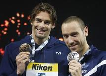O francês Camille Lacourt (esquerda) levanta sua medalha de ouro e posa com seu compatriota, o medalhista de prata Jeremy Stravius, após vencer os 50m peito nos campeonatos mundiais em Barcelona, Espanha. REUTERS/Albert Gea