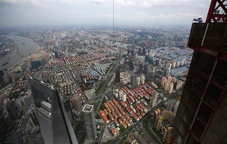 A photographer takes pictures of downtown Shanghai from the top Shanghai Tower, which is undergoing construction, during a media tour, August 2, 2013. REUTERS/Carlos Barria