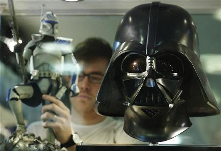 Employee Simon Domoney adjusts a Captain Rex figure alongside a scale replica of Star Wars character Darth Vader's helmet at the Forbidden Planet memorabilia and comic store in London May 11, 2013. REUTERS/Luke MacGregor