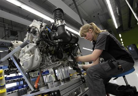worker assembles an engine for a new porsche 918 spyder sports car at the production