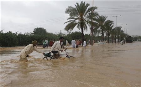 Men push their bicycles through flood waters on the outskirts of Karachi August 4, 2013. REUTERS/Akhtar Soomro