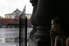 Девушка курит, прячась от дождя, на Красной площади в Москве 7 августа 2007 года. Рабочая неделя принесет в Москву небольшое потепление, но осадки в российской столице продолжатся, прогнозируют синоптики. REUTERS/Denis Sinyakov