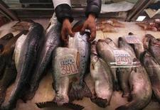 Продавец торгует рыбой на рынке в Санкт-Петербурге 5 апреля 2012 года. Рост потребительских цен в России в июле ускорился до 0,8 процента к предыдущему месяцу, замедлившись в годовом выражении до 6,5 процента, сообщил Росстат. REUTERS/Alexander Demianchuk