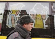 Полицейский проходит мимо автобуса, который отправляется в тур по Москве в поддержку осужденных участниц феминистской панк-группы Pussy Riot 31 марта 2012 года. Власти Украины начали расследование в отношении американской поп-панк группы Bloodhound Gang, которой запретили выступать российские власти в ответ на выходки музыкантов, подтёршихся триколором на концерте в Одессе и помочившихся на украинский жёлто-голубой флаг в Киеве. REUTERS/Denis Sinyakov