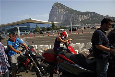 A woman rests on her scooter as she waits in line to enter Spain at its border with the British territory of Gibraltar in front of the Rock (rear), a monolithic limestone promontory in Gibraltar, south of Spain August 5, 2013. REUTERS/Jon Nazca
