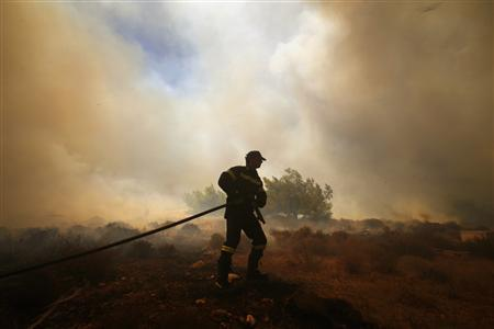 A Greek firefighter carries a hose as a forest fire rages in Marathon near Athens August 5, 2013. REUTERS-Yannis Behrakis