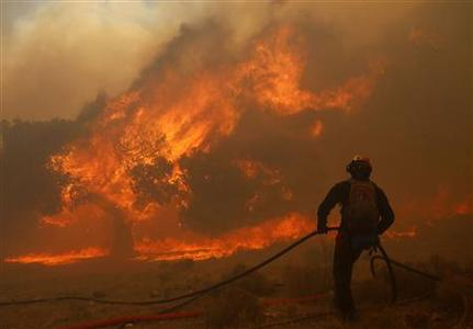 A Greek firefighter collects a water hose after running out of water as a forest fire rages in Marathon near Athens August 5, 2013. REUTERS-Yannis Behrakis
