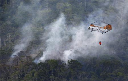 A U.S. military helicopter fights the fire at the crash site, following a crash by another U.S. military CH-46 helicopter, inside the U.S. Marine's Camp Hansen in central Okinawa, on Japan's southern island, in this photo taken by Kyodo August 5, 2013. A U.S. military helicopter crashed on Japan's southern island of Okinawa on Monday, Japanese officials said, an incident that could add to anger over the concentration of U.S. military bases on the island. REUTERS/Kyodo