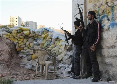 Free Syrian Army fighters take cover near sandbags in Ashrafieh, Aleppo August 5, 2013. REUTERS/Aref Hretani