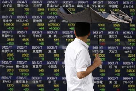 A pedestrian holding an umbrella walks past a stock quotation board displaying various stock prices outside a brokerage in Tokyo July 29, 2013. REUTERS/Yuya Shino