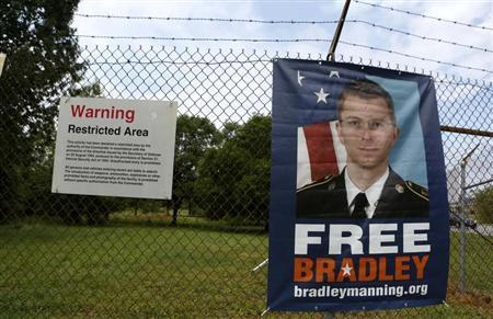 A poster with the face of U.S. Army Private First Class Bradley Manning is attached to the fence outside the main gate at the U.S. Army's Fort George G. Meade in Maryland, June 3, 2013. REUTERS/Larry Downing
