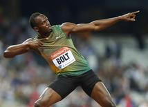 Jamaicano Usain Bolt posa para fotos após vencer a corrida de 100m durante encontro de atletismo britânico, no Estádio Olímpico, em Londres. Bolt será o astro inconteste do Mundial de Atletismo de Moscou neste mês, um evento esvaziado por uma série de casos de doping e contusão, e parece que só uma largada queimada, como ocorreu há dois anos na Coreia do Sul, poderá impedir o jamaicano de levar o título dos 100 metros. 26/07/2013. REUTERS/Andrew Winning