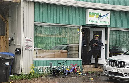 Police stand in front of the Reptile Ocean store in Campbellton, New Brunswick August 5, 2013 after an incident in which an African rock python escaped its enclosure, got into the store's ventilation system and apparently strangled two young boys as they slept. REUTERS/Tim Jaques/The Tribune/Telegraph Journal