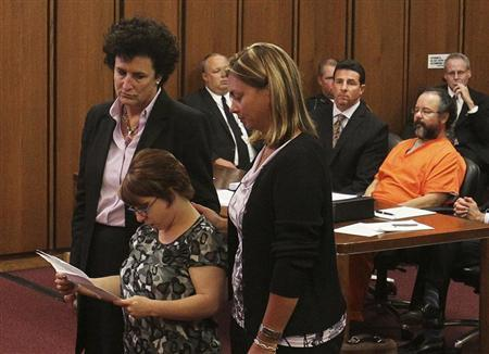 Michelle Knight (2nd from left) reads statements while supported by her attorney (L) and friend as her accused assailant Ariel Castro (R) sits in the courtroom during Castros sentencing of kidnapping, rape and murder in Cleveland, Ohio August 1, 2013. REUTERS/Aaron Josefczyk
