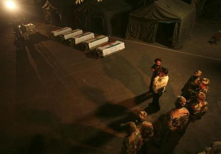 Indian army soldiers stand near the coffins of their colleagues during a wreath laying ceremony in Poonch district, northwest of Jammu August 6, 2013. REUTERS/Mukesh Gupta
