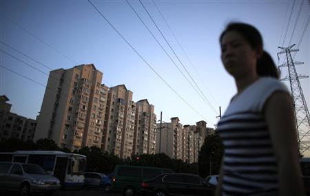 A woman walks by a residential area at the Pudong district of Shanghai July 18, 2013. REUTERS/Carlos Barria