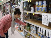 A woman browses for milk powder at a stand with a food recall notice from Nutricia in a supermarket in Huntly, Waikato Region in New Zealand August 6, 2013. REUTERS/Nigel Marple