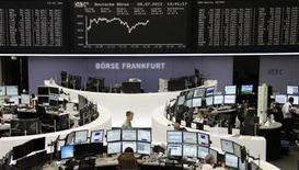 Traders are pictured at their desks in front of the DAX board at the Frankfurt stock exchange July 9, 2013. REUTERS/Remote/Stringer