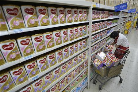 A sales assistant takes down Dumex milk powder products from shelves, which were included in a recall program by Fonterra, at a supermarket in Taiyuan, Shanxi province August 5, 2013. REUTERS/Stringer
