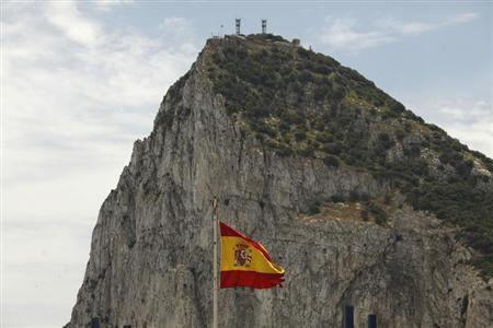 A Spanish flag flies in front of the Rock of Gibraltar as seen from La Linea de la Concepcion, southern Spain May 25, 2012. REUTERS/Jon Nazca