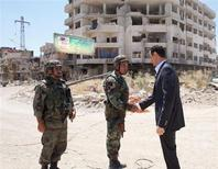 Syria's President Bashar al-Assad (R) shakes hands with a military personnel during his visit to a military site at Darya area, on the occasion of the 68th anniversary of army day, in this handout photograph distributed by Syria's national news agency SANA on August 1, 2013. REUTERS/SANA/Handout via Reuters