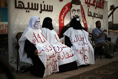 Female supporters of deposed Egyptian President Mohamed Mursi wear white cloths during a protest in Cairo July 9, 2013. REUTERS/Suhaib Salem