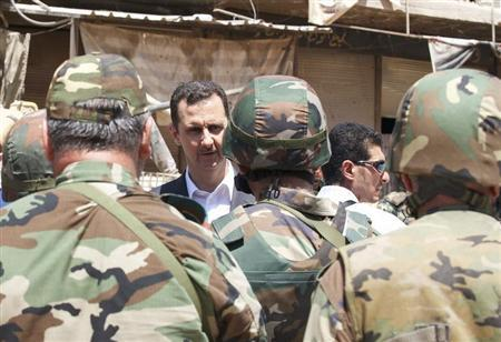 Syria's President Bashar al-Assad (C) chats with military personnel during his visit to a military site in the town of Daraya, southwest of Damascus, on the 68th anniversary of army day, in this handout photograph distributed by Syria's national news agency SANA on August 1, 2013. REUTERS/SANA/Handout via Reuters