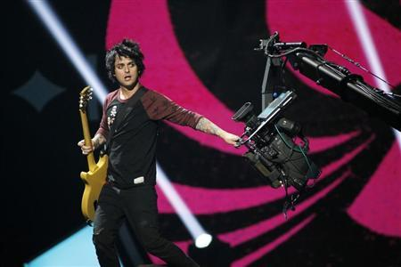 Green Day lead vocalist and guitarist Billie Joe Armstrong grabs a camera during the 2012 iHeart Radio Music Festival at the MGM Grand Garden Arena in Las Vegas, Nevada September 21, 2012. REUTERS/Steve Marcus