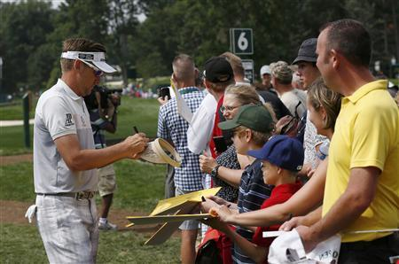 England's Ian Poulter signs autographs for fans after playing the sixth hole during a practice round for the 2013 PGA Championship golf tournament at Oak Hill Country Club in Rochester, New York August 7, 2013. REUTERS/Mathieu Belanger