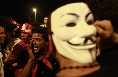 An anti-government protester wears a Guy Fawkes mask as another shouts slogans during a demonstration in Tunis August 6, 2013. REUTERS/Anis Mili