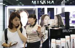 A tourist (L) shops at a store of Missha, a budget brand of Able C&C in central Seoul August 6, 2013. REUTERS/Lee Jae-Won