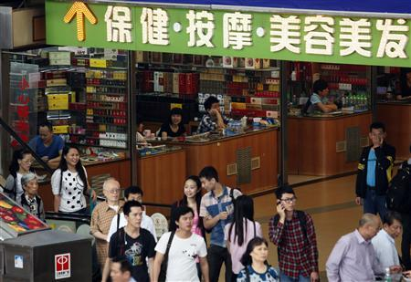 Shoppers walk past small shops at an underground mall in Zhuhai, neighbouring Macau April 29, 2013. REUTERS/Staff