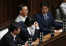 Japan's Prime Minister Shinzo Abe (R) talks with the Minister of Economy, Trade and Industry Toshimitsu Motegi (L) and other lawmakers at the lower house parliamentary session in Tokyo August 7, 2013. REUTERS/Issei Kato
