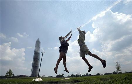 Friends Grace Greenwood (L) and Alex Place, both of Arlington, Virginia, leap into a water sprinkler for a ''high ten'' during heat wave at the Washington Monument in Washington July 18, 2013. REUTERS/Kevin Lamarque