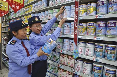 Chinese commercial law enforcement personnel inspect milk powder products at a supermarket in Lianyungang, Jiangsu province August 6, 2013. REUTERS/China Daily