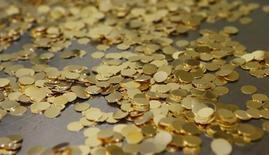 Золотые заготовки для монет на монетном дворе в Вене 23 апреля 2013 года. Цены на золото отыграли потери, понесенные в начале сессии, за счет слабого доллара и покрытия коротких позиций. REUTERS/Leonhard Foeger