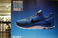 Cliente experimenta par de tênis da Nike dentro de loja em distrito comercial de Pequim, China, 6 de agosto de 2013. Uma recuperação surpreendentemente firme das exportações e importações da China em julho ofereceu alguma esperança de que a segunda maior economia do mundo pode estar se estabilizando após mais de dois anos de crescimento lento. 06/08/2013 REUTERS/Kim Kyung-Hoon