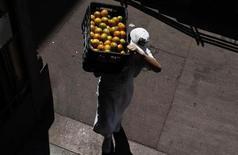 Homem carrega caixa de laranjas no Mercado Municipal, em São Paulo. A produção comercial de laranja em São Paulo, maior produtor brasileiro da fruta, foi estimada em 296,8 milhões de caixas de 40,8 kg na temporada em 2013/14, queda de quase 10 por cento ante a previsão de maio, devido a problemas climáticos, disse nesta quinta-feira a Companhia Nacional de Abastecimento (Conab). 4/08/2012. REUTERS/Nacho Doce