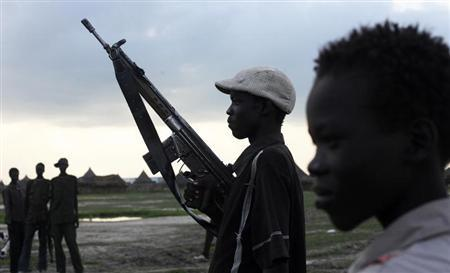 A youth from the Luo Nuer tribe carries his gun as he walks home in Yuai Uror county, in South Sudan, July 23, 2013. REUTERS/Andreea Campeanu