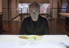 "Chef Ferran Adria poses by a table projecting food being eaten, at the exhibition ""elBulli: Ferran Adria and The Art of Food"" at Somerset House in London July 4, 2013. REUTERS/Neil Hall"