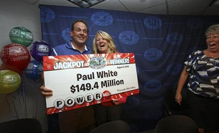 Paul White (L), 45, from Ham Lake, Minnesota, stands with his partner Kim VanReese (C) and co-worker Nancy Bowen (R) as he holds a check for his $149.4 million portion of a $448.4 million Powerball jackpot prize at a news conference at Minnesota State Lottery headquarters in Roseville, August 8, 2013. REUTERS/Eric Miller