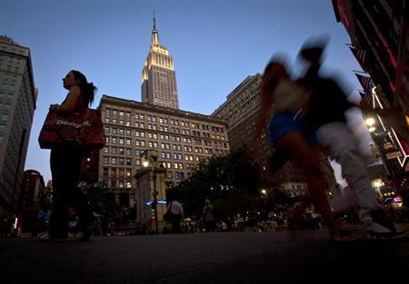 People walk through Herald Square under the Empire State Building in New York, July 24, 2013. REUTERS/Carlo Allegri