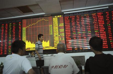 An investor walks past as others look at an electronic board showing stock information at a brokerage house in Wuhan, Hubei province July 11, 2013. REUTERS/Stringer/Files
